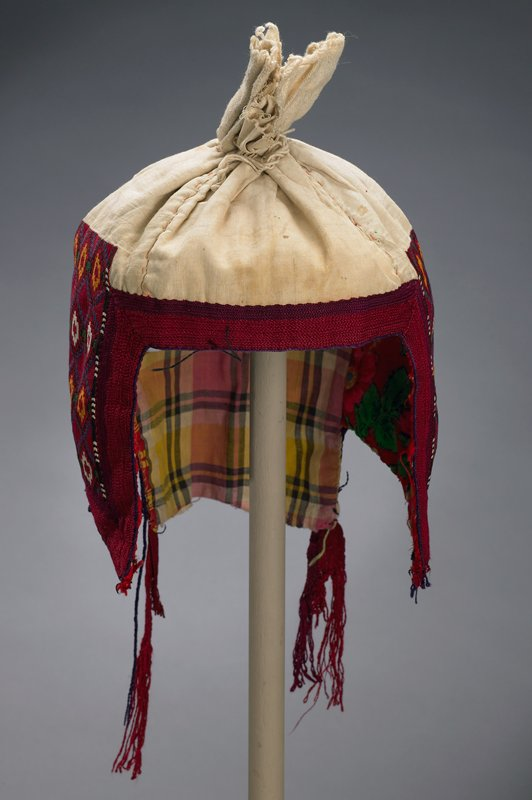 """red embroidery with muslin and coarse weave cotton that is gathered to form cap; ear flaps heavily embroidered with rows of tiny chain stitch forming double diamonds in black and blue with yellow and white; edged in wide 1"""" trim; lined in red floral wool and yellow plaid cottons; inter lining of coarse weave, natural cotton; trim extends 7-8""""after garment ends"""