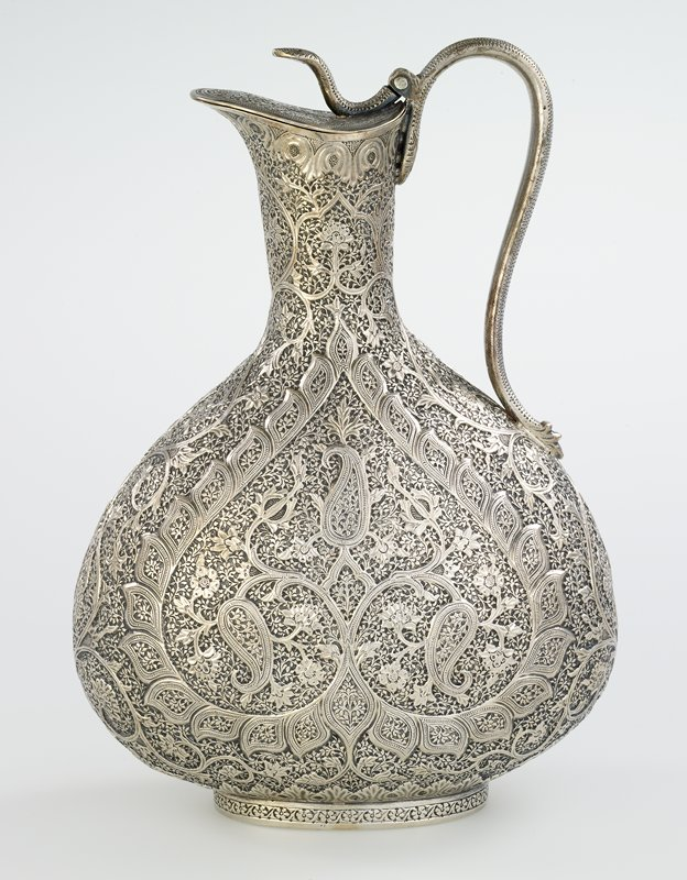 silver claret jug with hinged cover; overall floral motif, highly decorative, large upside down heart at each side, raised cobra forms the handle, hinge and central decorative element on top of the cover