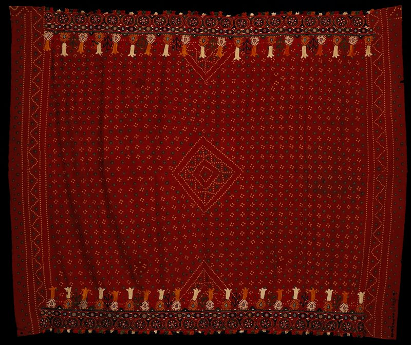 """two handstitched panels of batik with embroidery on selvage edges; dark red field with green and yellow dots overall with center geometric pattern; lower left edge has rows of markings 9"""" long; either end has applied silk fringe in dark blue, ecru, red, orange and green; 2"""" horizontal band of circles in same colors; center mirror; continuing inward, 1 1/2"""" band and 5/8"""" mirrors enclosed in oval silk embroidery with tear shaped mirror, above horizontal row of floral embroidery in similar colors"""