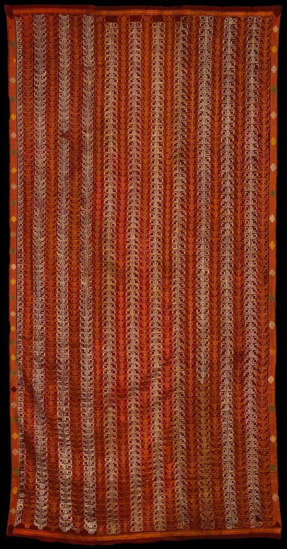 three panels hand stitched together; overall silk square shaped embroidery patterns forming vertical stripes in orange, yellow, off-white and green on rust; top and bottom embroidered geometric borders; sides have diamond shapes of various sizes