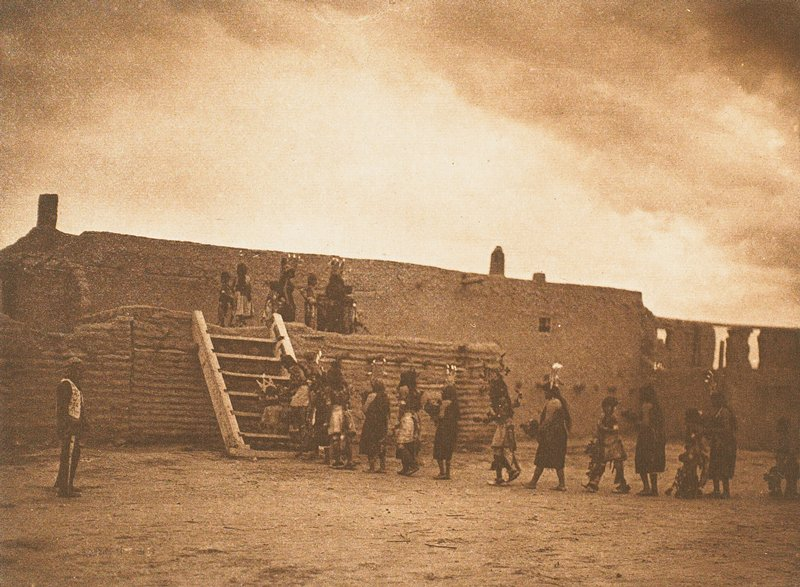 people in costumes with headdresses walking in a line up a wide ladder to the top of an adobe structure