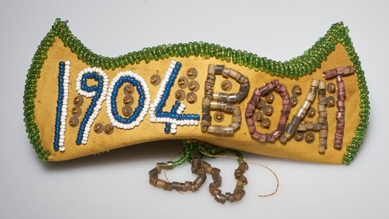 "canoe shaped; tan fabric; green bead edging; three dangling bead loops on bottom; ""1904 BOAT"" on one side; flag and ""FAIR"" on other side"