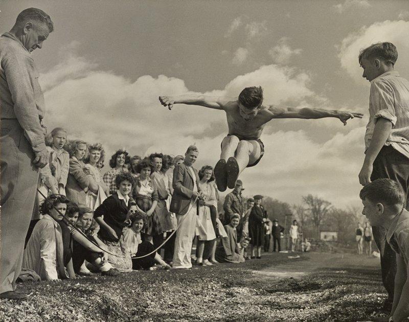 shirtless young man with legs together and arms outstretched, jumping; two boys at L and other people (mostly young women) at L look on