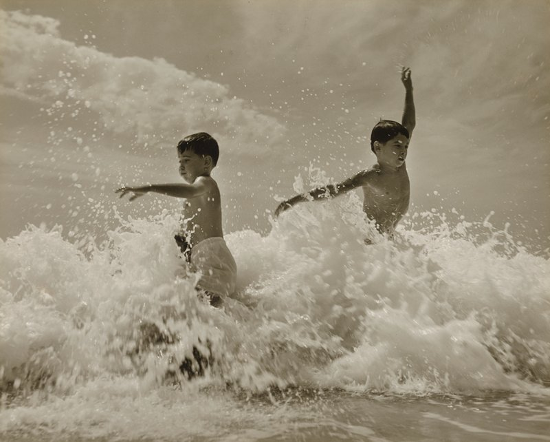 two little boys playing in the surf; boy at L wears light-colored swimming trunks