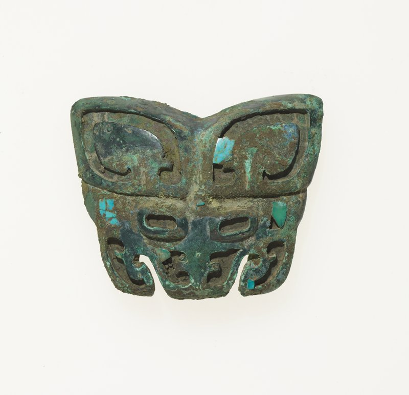 The mask of an ordinary t'ao-t'ieh was originally inlaid with turquoise, of which only remnants are left. Patina green.