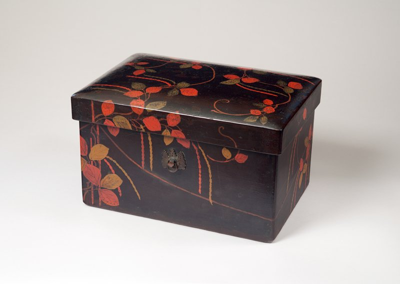 dark brown box with design of reddish orange and gold leaves; red beans; rectangular-shaped; pair of metal ornaments with a ring on long sides of box