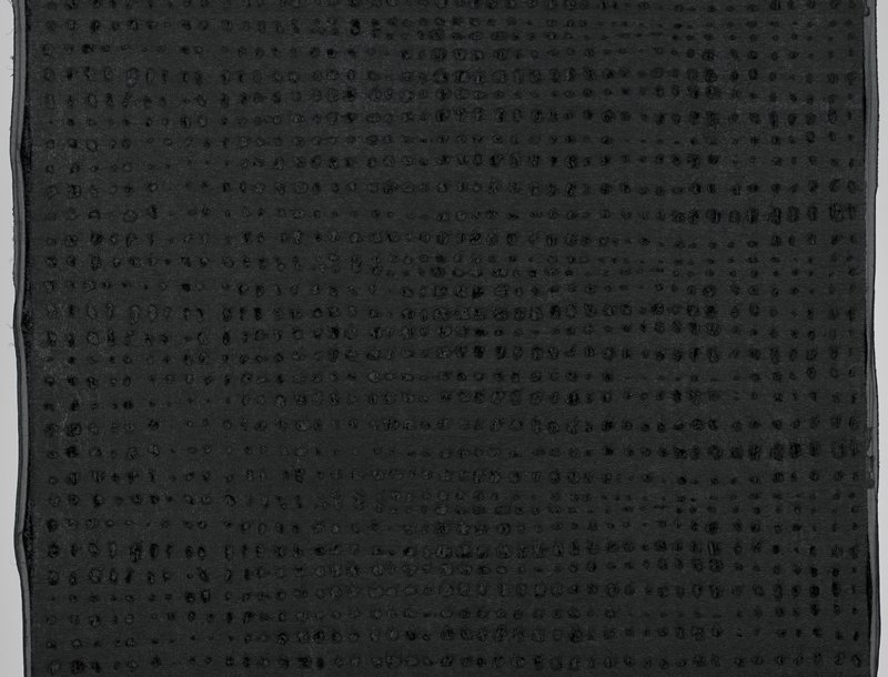 black pile fabric with smooth backing; leather-like surface with abraded regular holes in rows