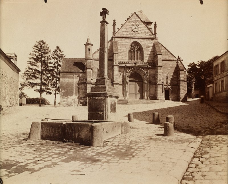 brick church with triangular pediment; cobblestone plaza in front of church with column topped with cross