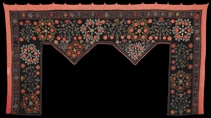 roughly U-shaped, with open central bottom section and two triangular descending elements at center; black ground decorated with multicolored (primarily salmon) flower sprays and medallions; salmon pink fabric trim