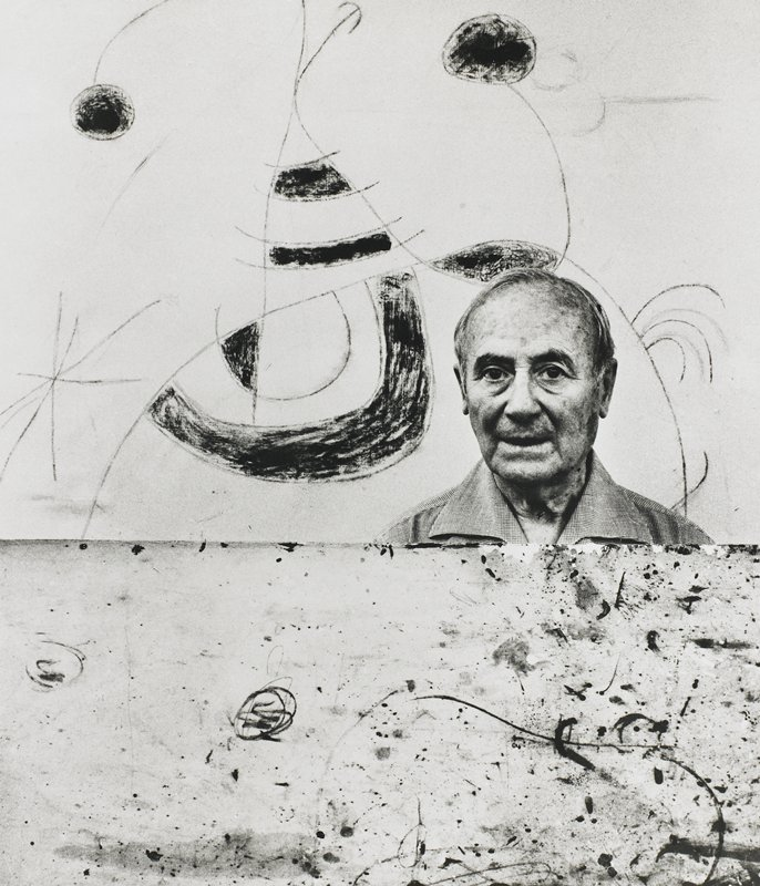 balding man with blotchy skin in front of an abstract drawing; another drawing in front of man at breastbone level