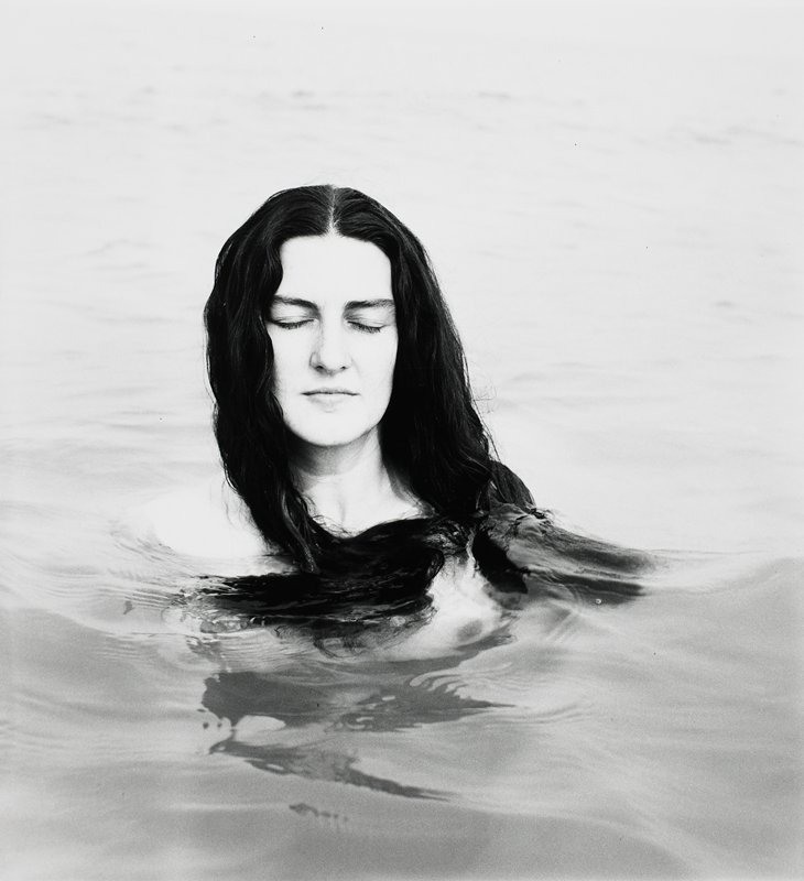 head and shoulders of a woman above water; woman has long wavy dark hair, parted in the middle; eyes closed