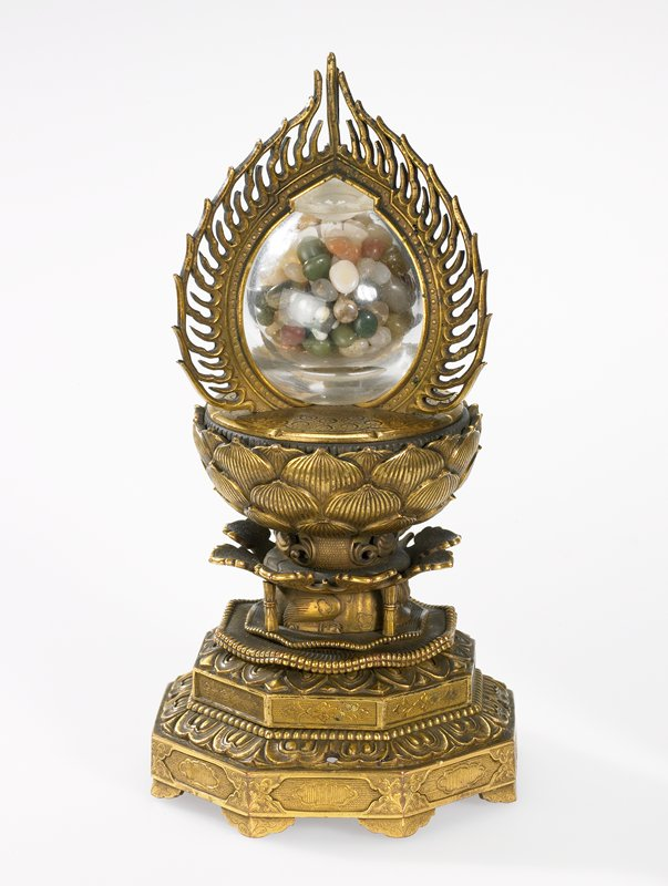 "octagonal stepped base with lotus flower at top of base; clear glass globe at top with three vertical metal ""flames"" around it; glass globe filled with multicolored pebbles"