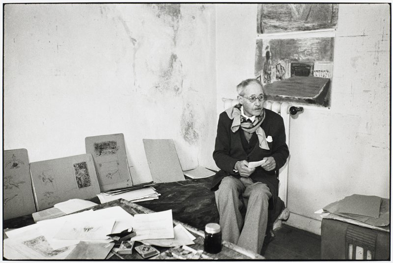 Bonnard seated in his studio; drawings and sketches on walls and tables; two drawings on wall behind head