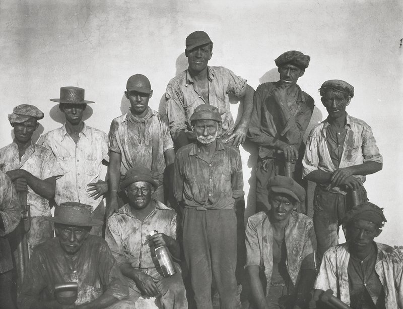 eleven men, seated and standing, with soot-covered arms, faces and clothes