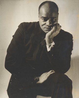 black man wearing a dark suit; PR elbow and PL hand resting on PL thigh