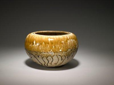globular body with large circular mouth; yellowish brown glaze on top half and brown drips on bottom unglazed half