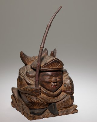 one of a pair of auspicious folk art figures: Doikoku and Ebisen; man with fish and pole
