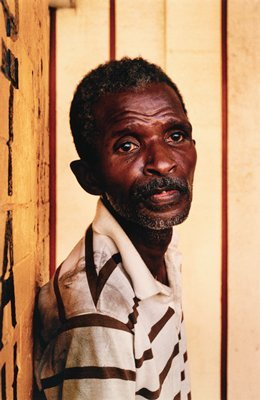 portrait of middle-aged African man from mid-torso up and from PR side with his head turned towards camera; wearing beige shirt with brown stripes; matted